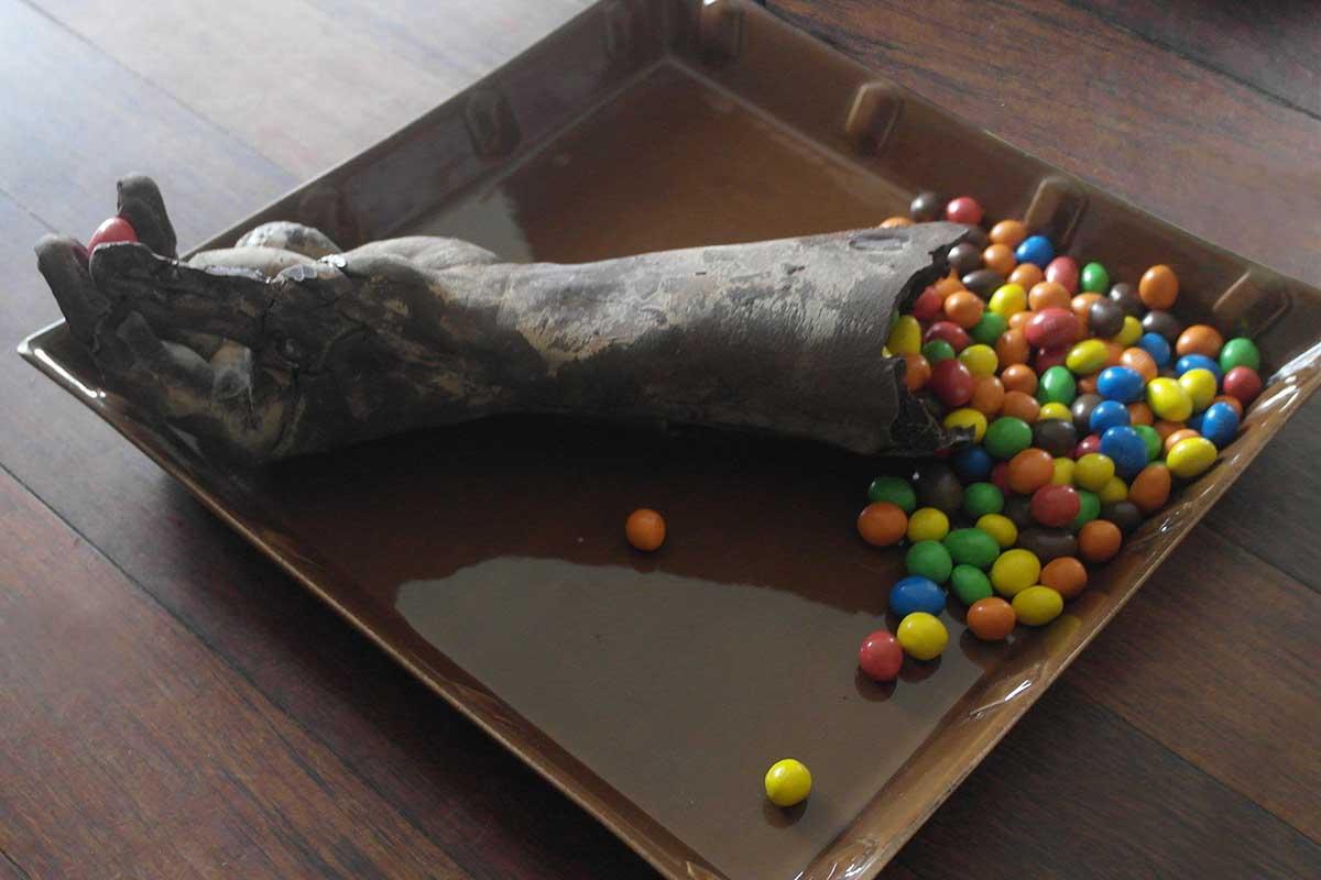 Moulage d'une main en chocolat noir et confiserie M&M's